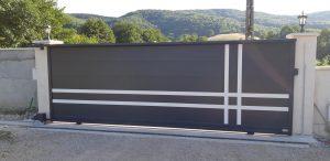 Portail coulissant aluminium Guzmania, posé par Design Fermetures, vu de l'intérieur avec son rail permettant l'ouverture